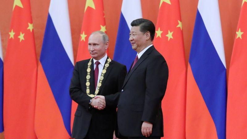 普京获颁中国友谊勋章后,与习近平握手。