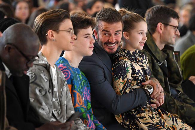 贝克汉家老么小哈泼坐在爸爸腿上看妈妈贝嫂的大秀。(Getty Images)