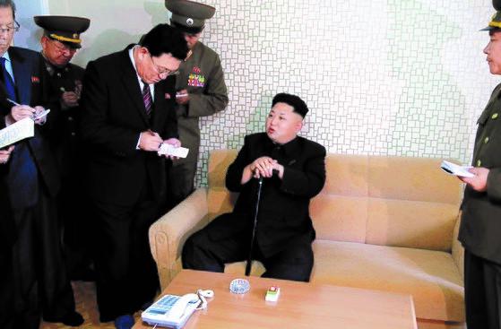 图为2014年10月,朝鲜国防委员会第一委员长金正恩在消失40天后拄着拐杖访问平壤卫生科学工作者住宅小区,进行现场指导。中央照片库