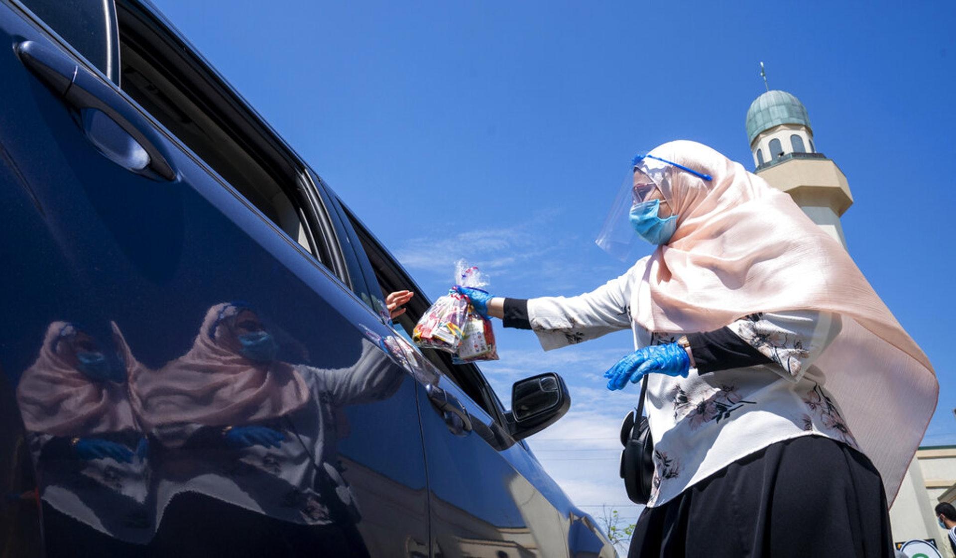加拿大新冠肺炎疫情:图为5月24日加拿大多伦多一个伊斯兰社区团体的成员在开斋节时将糖果送赠给车上的儿童。(AP)