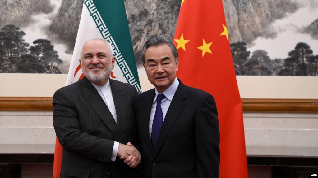2019年12月31日,中国外长王毅(右)与伊朗外长穆罕默德·贾瓦德·扎里夫(Mohammad Javad Zarif)在北京钓鱼台国宾馆举行的会议上握手。