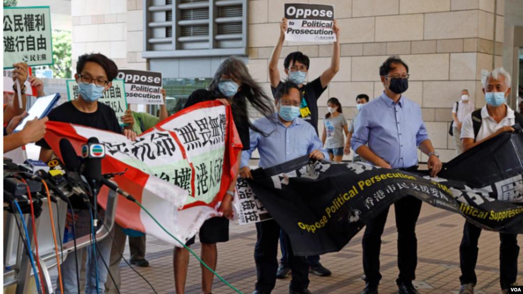 梁国雄(左二)等民主派积极分子香港区域法院外手持横幅抗议政治迫害。(2020年7月30日)