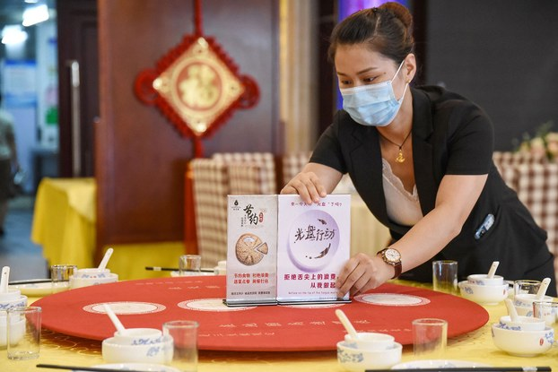 """2020年8月13日,一名工作人员在河北邯郸一家餐厅餐桌上摆放节约粮食的宣传牌,倡导""""光盘""""行动杜绝""""舌尖上的浪费""""。(AFP)"""