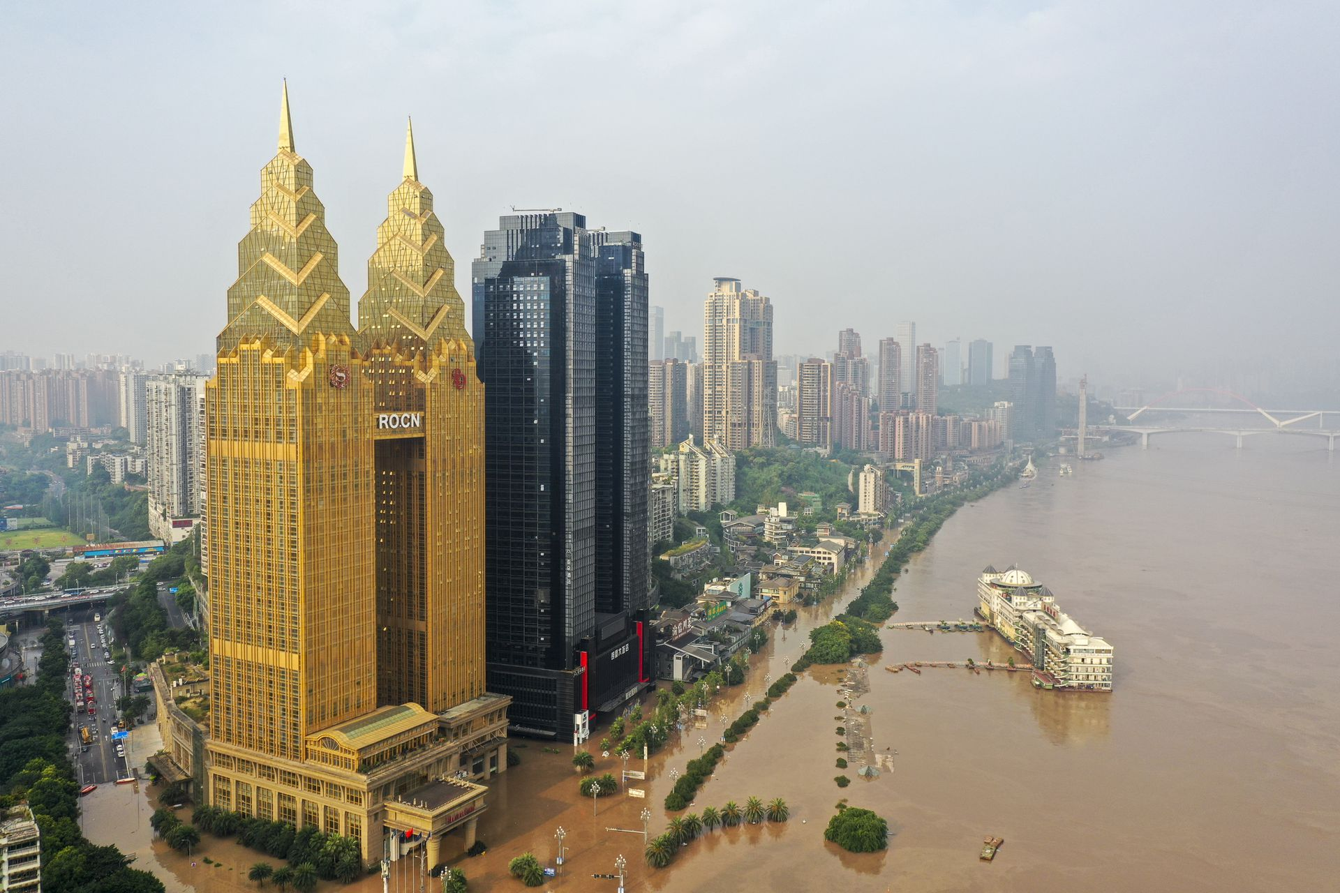 """受""""长江2020年第5号洪水""""""""嘉陵江2020年第2号洪水""""影响,8月18至20日,中国西南城市遭遇罕见的洪水。重庆主城沿江迎来历史罕见过境洪水,8月20日上午,长江、嘉陵江洪水洪峰通过重庆主城中心城区,随后水位持续回落,被淹没的沿江道路缓慢露出水面,城区部分低洼地带的积水逐渐退去。(新华社)"""