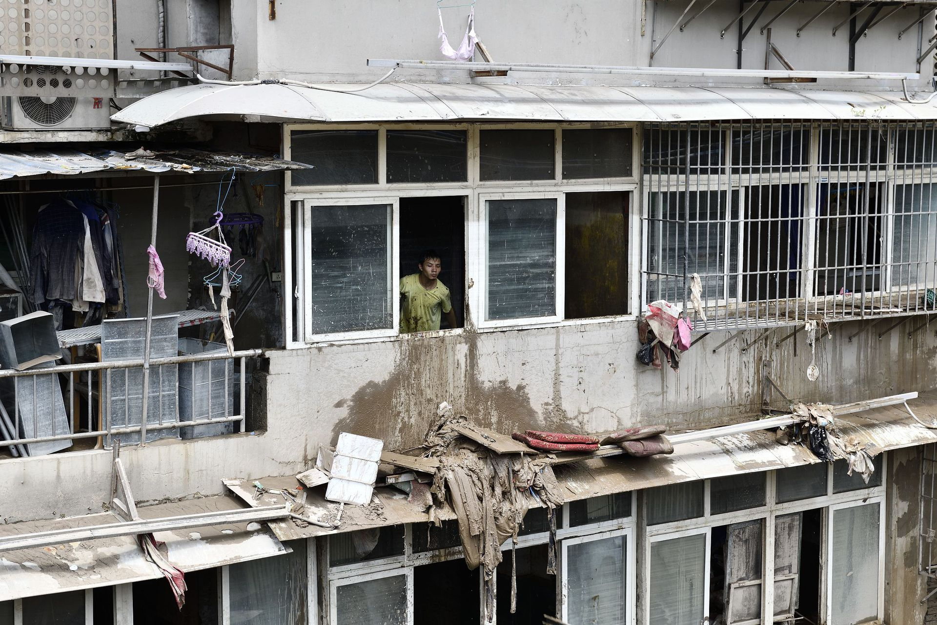 重庆渝中区长江滨江路上,一幢居民楼在此次洪峰被淹至两楼,图为该居民楼阳台上的居民。