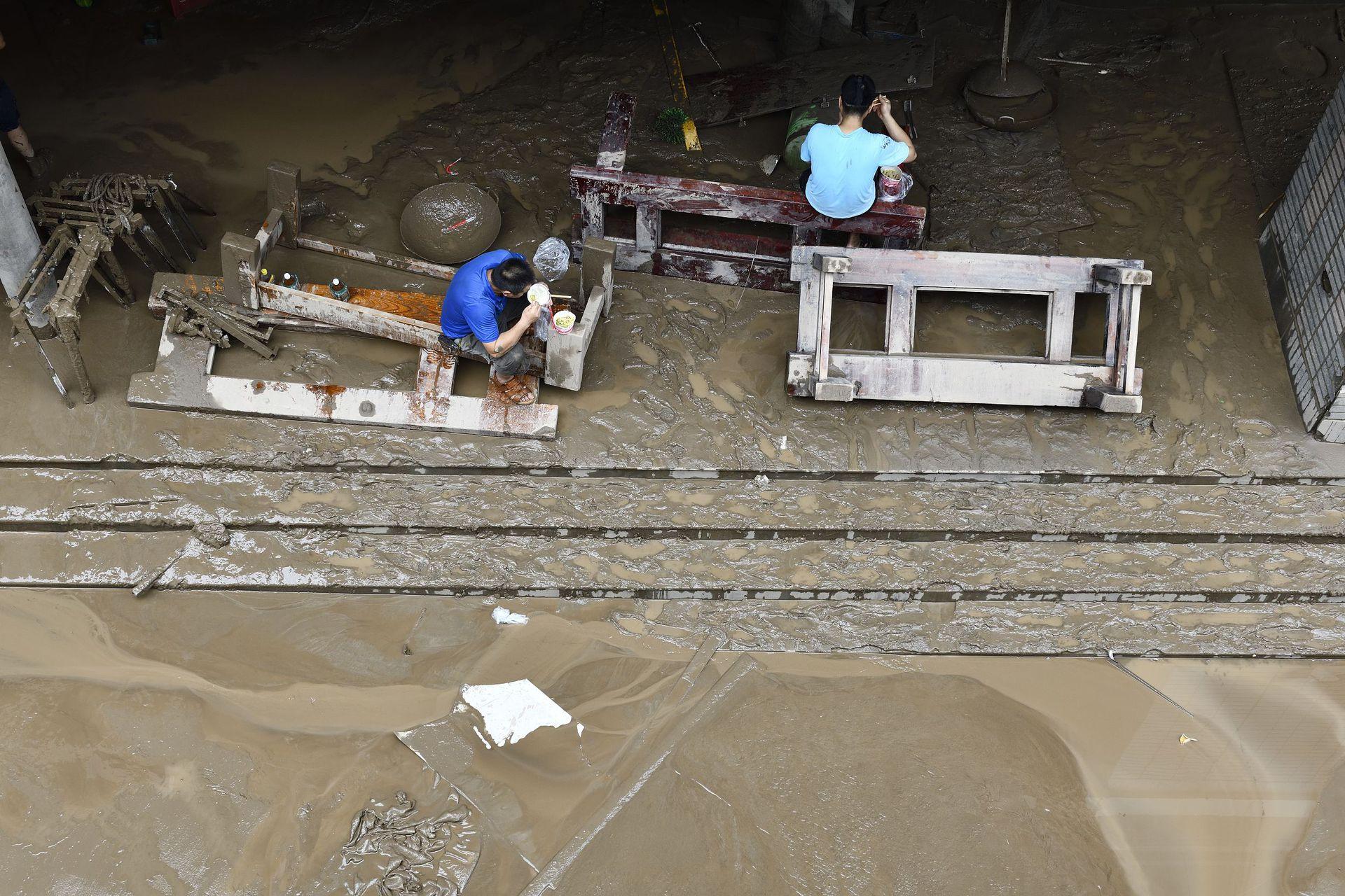 一家被淹的商家内,两位工作人员正在吃盒饭。
