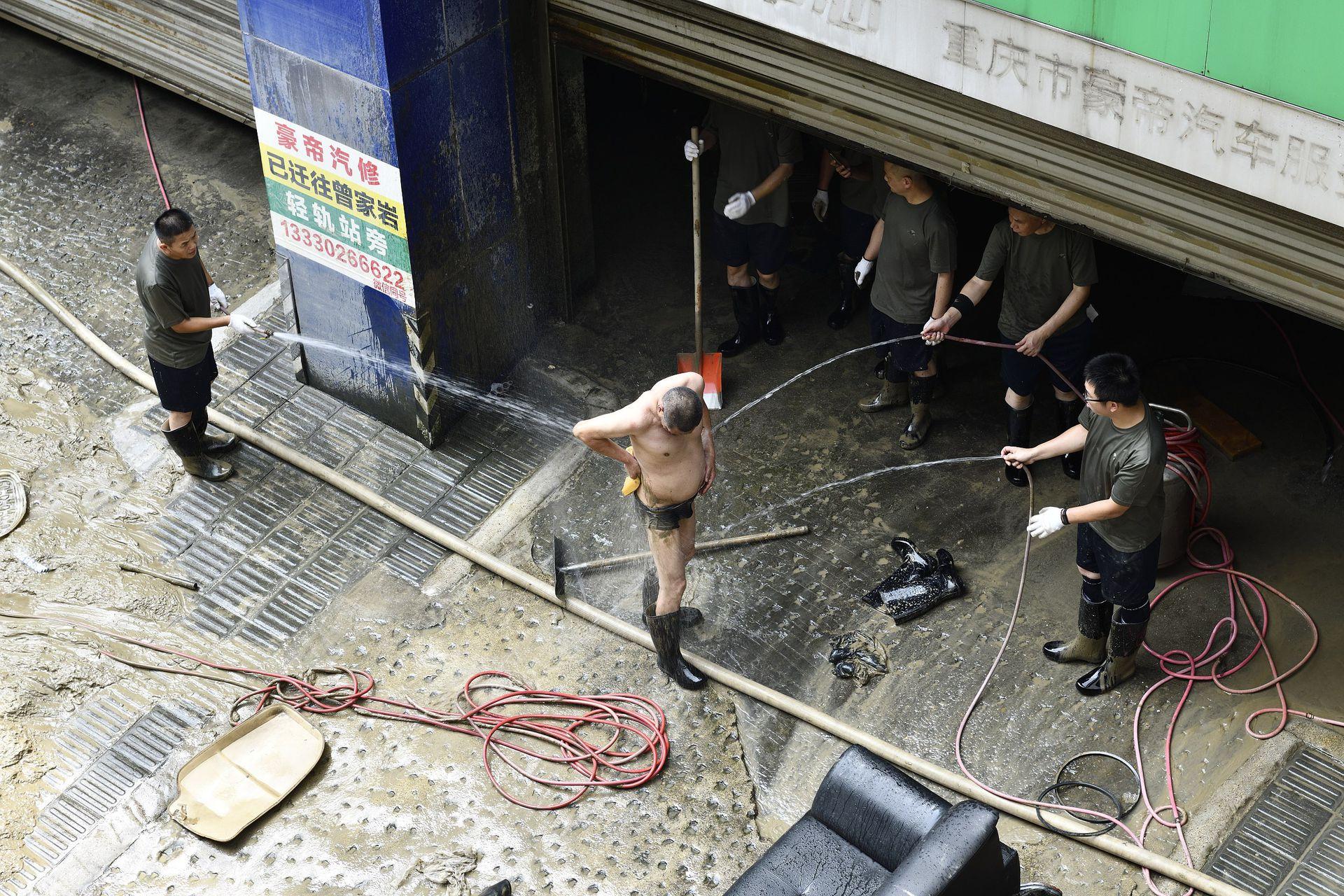 重庆渝中区嘉陵江滨江路上一位清淤工人摔入泥浆中后,三位同事正在为他清洗身体。