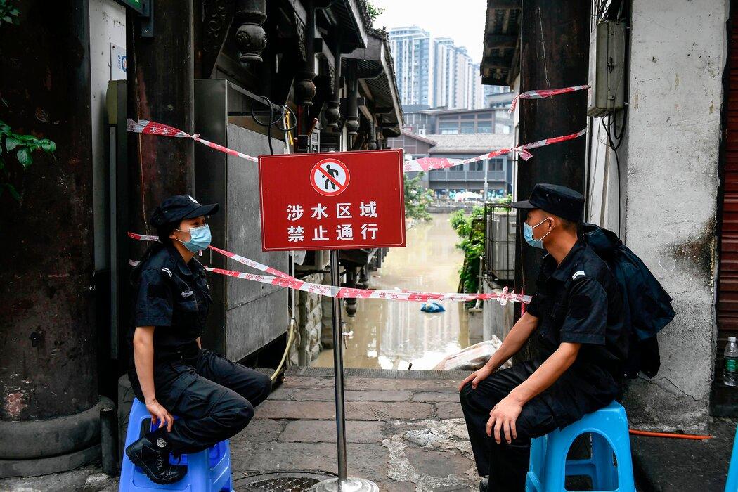 重庆的一条小巷因洪水而被封锁,保安在巷口警戒。
