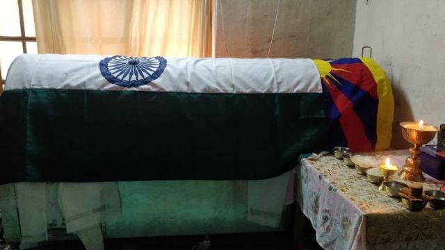 """丹增尼玛的棺椁上覆盖了三色的印度国旗和西藏传统的""""雪山狮子旗""""。"""