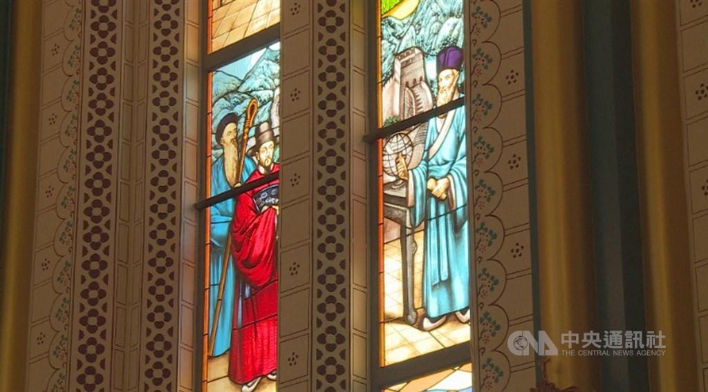 西什库教堂内有36根金黄与水蓝相间的柱子,搭配黄底红线的高耸圆弧尖顶,以及80面印有中西方风格图案的彩色玻璃花窗。图为花窗上分别身着明清两代服装的传教士,並有万里长城图案。中央社记者邱国强北京摄 109年10月7日