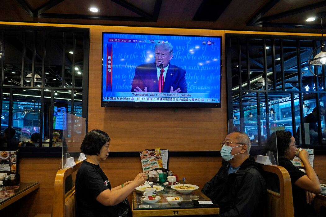 香港一家餐厅在播放美国总统大选辩论的新闻。闭门召开的中共会议与喧嚣的民主政治形成了鲜明对比。
