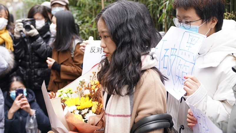 庭外支持者向弦子(化名)送上鮮花。