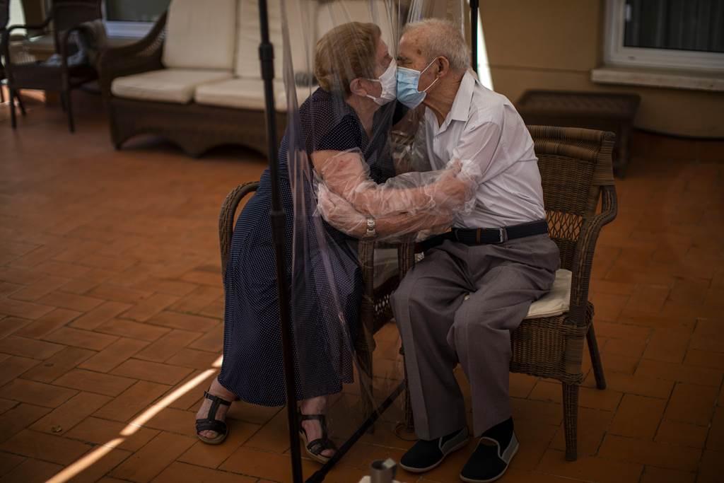 一对西班牙夫妇隔著防护隔离层相拥亲吻。