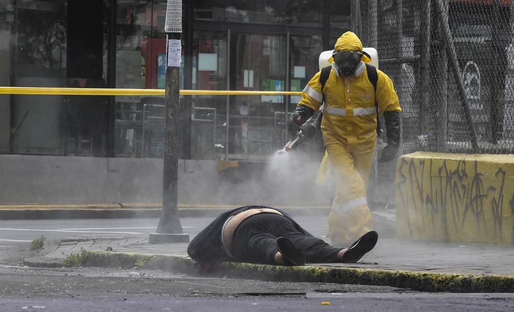 一名厄瓜多的法医人员正在替因新冠病毒病殁的死者喷洒消毒剂。