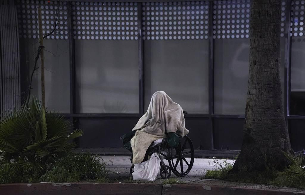一名内无家可归的新冠患者,在洛杉矶日落大道上坐著轮椅上淋著雨。