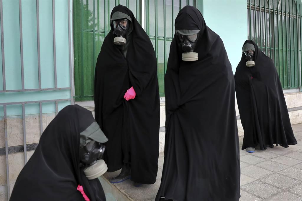 一名穿著特有的穆斯林外衣「卡多尔」、面带防毒面具的伊朗女士,正参加因新冠病殁者的丧礼。