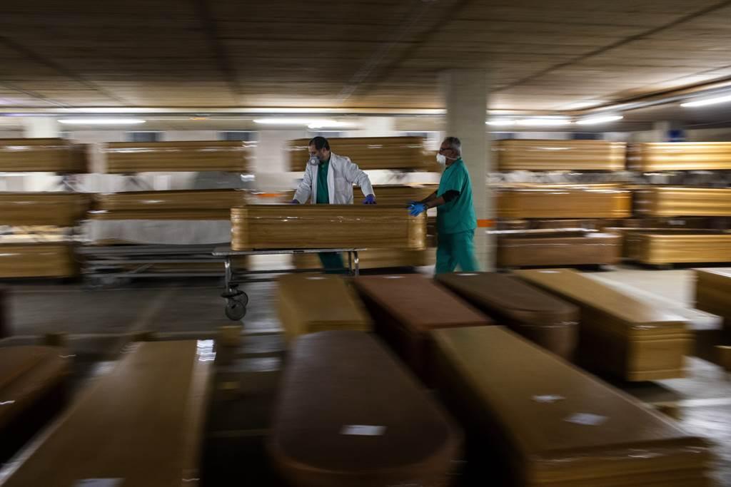 一名西班牙殡丧业者推著装有新冠患者遗体的棺材。