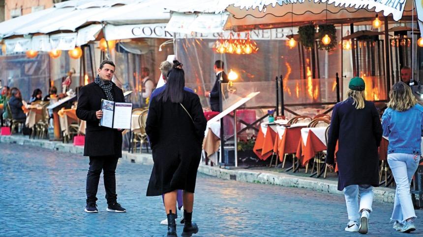 图为罗马纳沃纳广场一名侍应游说顾客进入餐厅用餐。