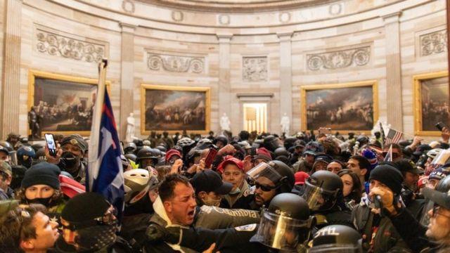 美国警察与闯入国会山的暴徒对峙。
