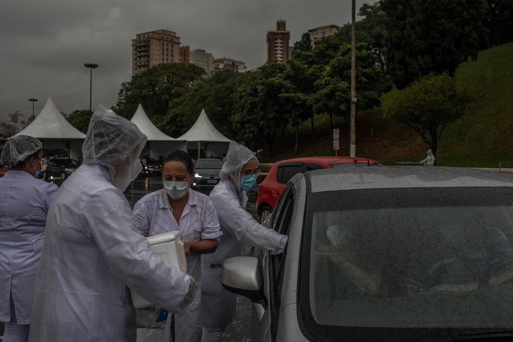 在圣保罗的一个免下车接种点,人们正在接种CoronaVac疫苗。