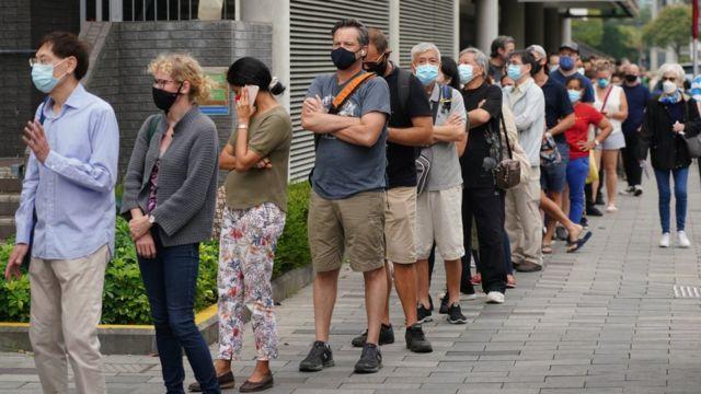香港市民在西区中山纪念公园体育馆社区疫苗接种中心门前排起长龙准备接种复必泰疫苗(中新社图片5/4/2021)