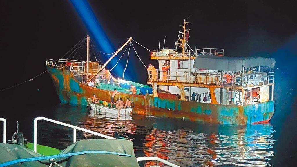 大陆渔船在东沙环礁违法越界捕鱼遭海巡署人员锁定并依法送办。(海巡署提供/李文正台北传真)