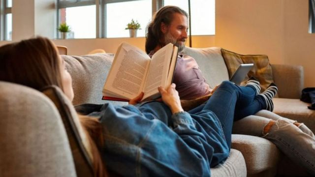 A man and a woman sit on a couch reading