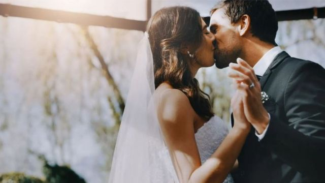 A couple in wedding dress and suit kissing