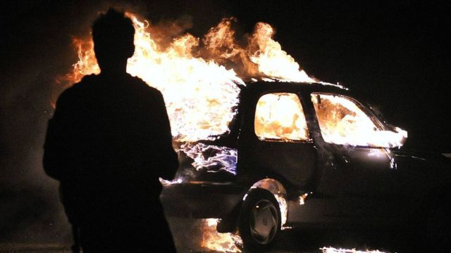 A person stands in front of a burning car at night