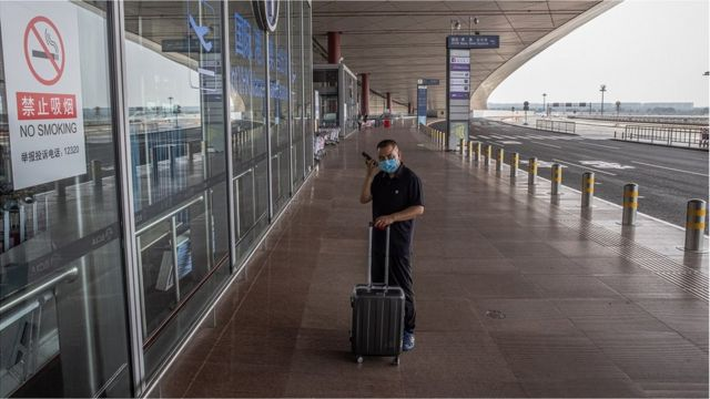 A passenger wearing a protective face mask stands at the entrance to the terminal 3 departure hall of Beijing Capital International Airport, amid the coronavirus pandemic in Beijing, China, 05 August 2021.