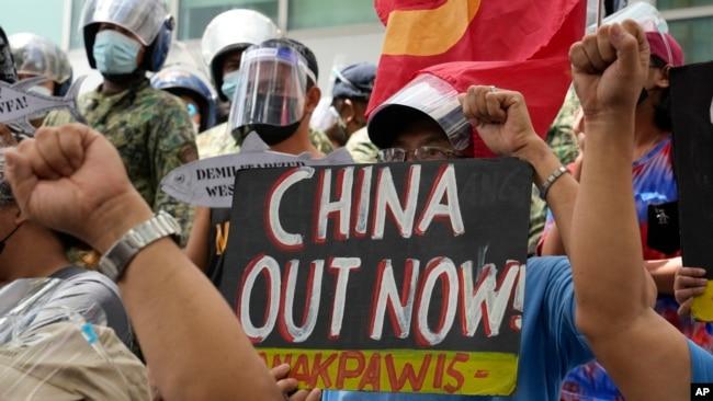资料照片:在海牙国际仲裁庭就菲律宾与中国海洋权利纠纷作出裁决五周年之际,抗议者举着标语在中国驻菲律宾大使馆位于马卡蒂市的领事馆外集会。(2021年7月12日)