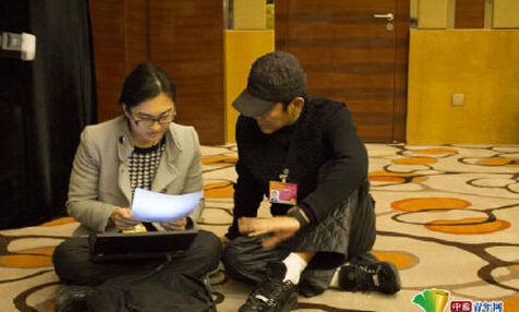 政协委员陈道明坐地上给两会记者改稿子