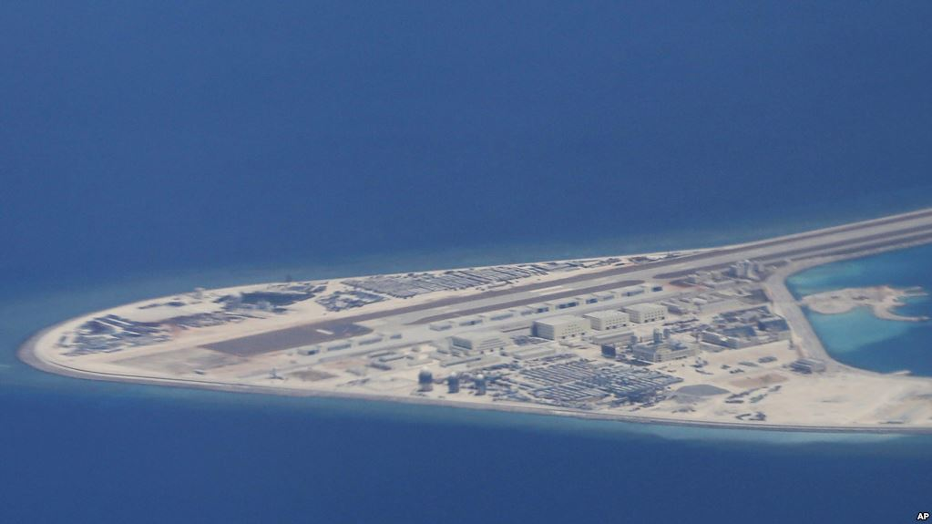 菲律宾空军一架运输机在南中国海南沙群岛的中国制造的人造岛礁渚碧礁上空飞越时拍摄的照片,显示人造岛礁上的简易机场和建筑物。(2017年4月21日)