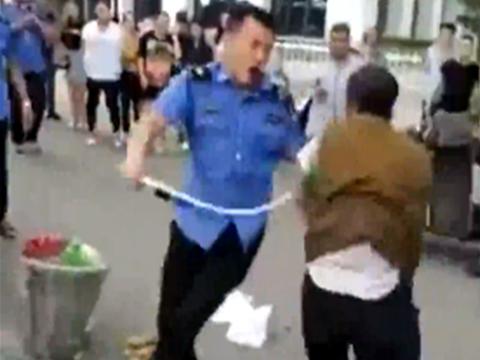 中国城管当街鞭抽商贩 打倒在地仍未收手