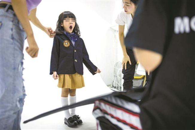 因为工作量大,专业童模在拍摄中打起哈欠。 (取材自广州日报)