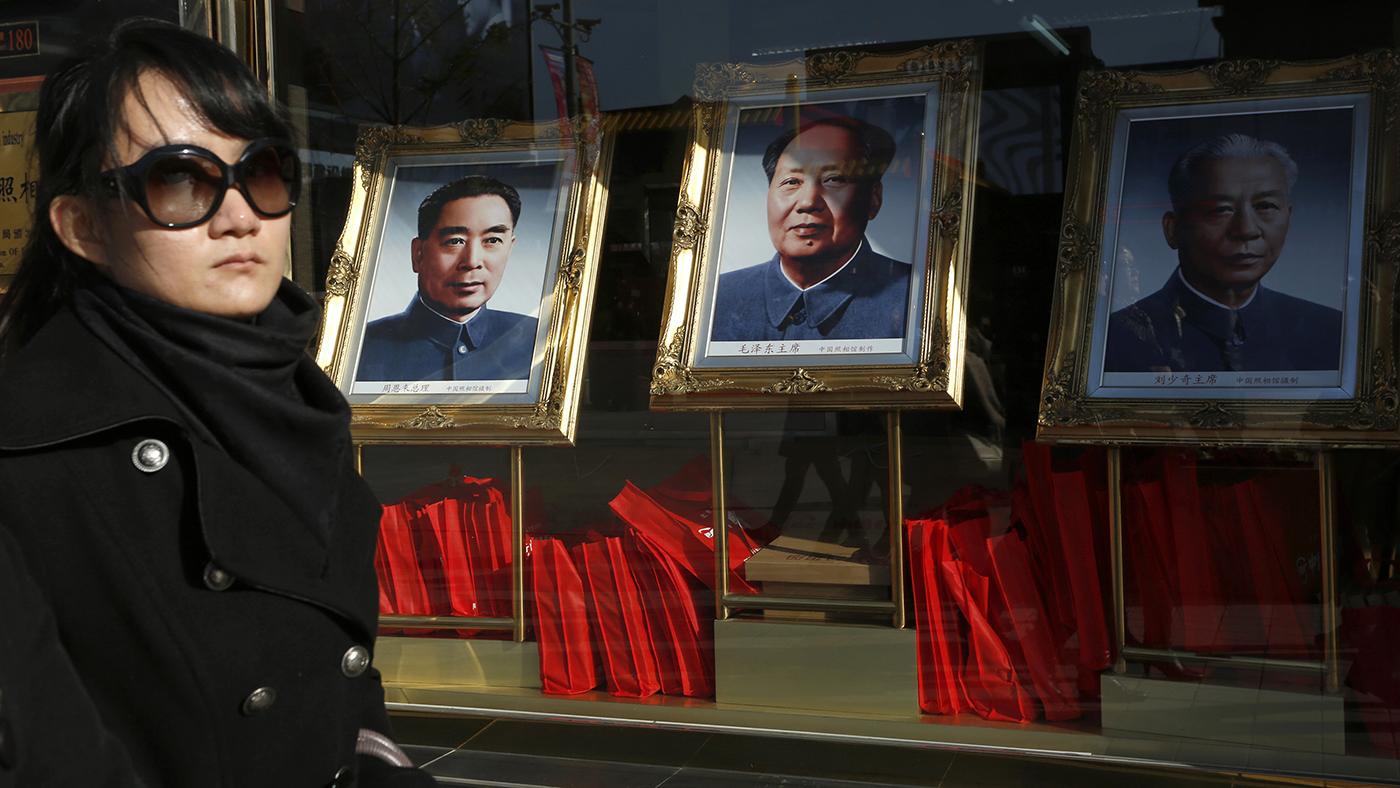 一名中国女子走过出售周恩来(左起)、毛泽东和刘少奇肖像的商场。(美联社)