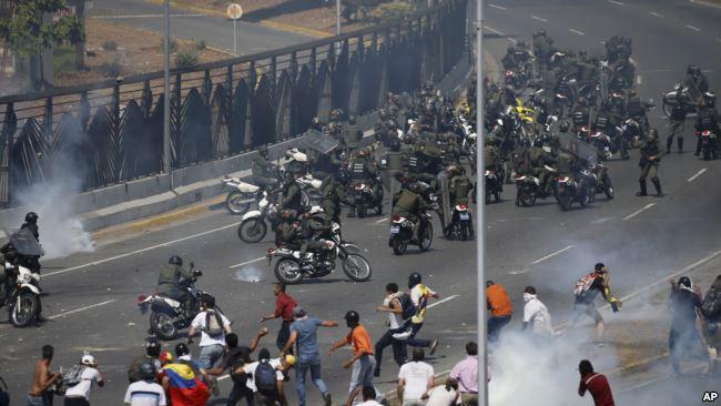 反对马杜罗的抗议者在加拉加斯一座空军基地外与支持马杜罗的军人对抗。(2019年4月30日)