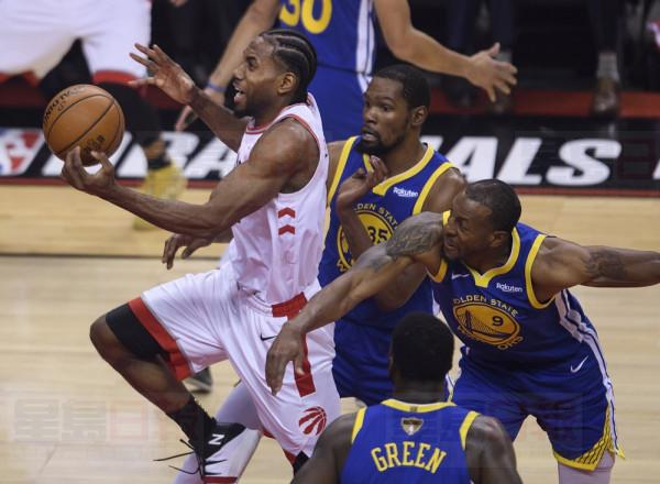 Toronto Raptors forward Kawhi Leonard (2) drives past Golden State Warriors forward Kevin Durant (35) and Warriors forward Andre Iguodala (9) during first half Game 5 NBA Finals basketball action in Toronto on Monday, June 10, 2019. THE CANADIAN PRESS/Nathan Denette