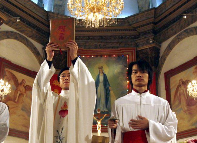 资料照: 北京天主教堂里的一名神职人员在做圣诞弥撒时高举中文版的圣经。(2007年12月24日)