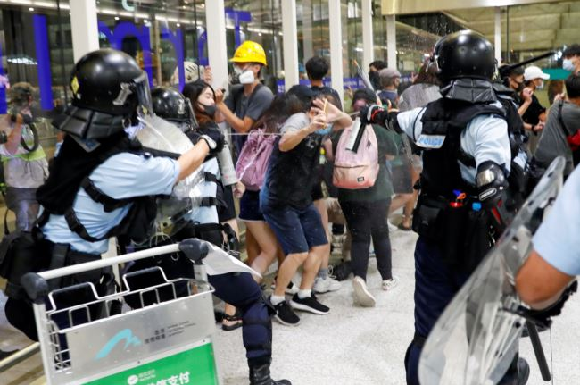 8月13日,防暴警察使用胡椒水驱散反送中大游行的抗议者。在此之前,一名女性抗议者在香港国际机场的集会中眼部受伤。