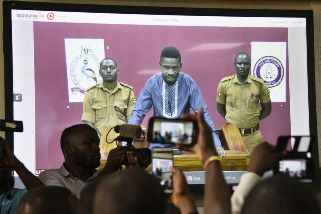 """乌干达歌手出身的反对派议员博比・瓦恩2019年5月2日视频""""出庭""""。瓦恩原名罗伯特・森塔穆,他常因批评总统穆塞韦尼而被逮捕。《华尔街日报》的报道说,警方与华为公司员工合作破解了瓦恩的通讯工具。"""