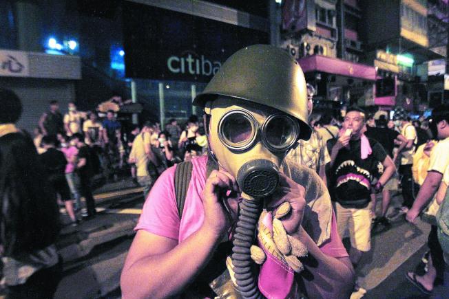 图为港警镇压抗议运动,商业区旺角的抗议者戴上防毒面具自保。(路透资料照片)