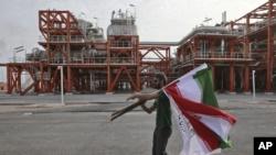 在伊朗波斯湾北部海岸南帕尔斯天然气田,一名伊朗工人在一家天然气精炼厂的落成典礼前举着伊朗国旗(2019年3月16日)。