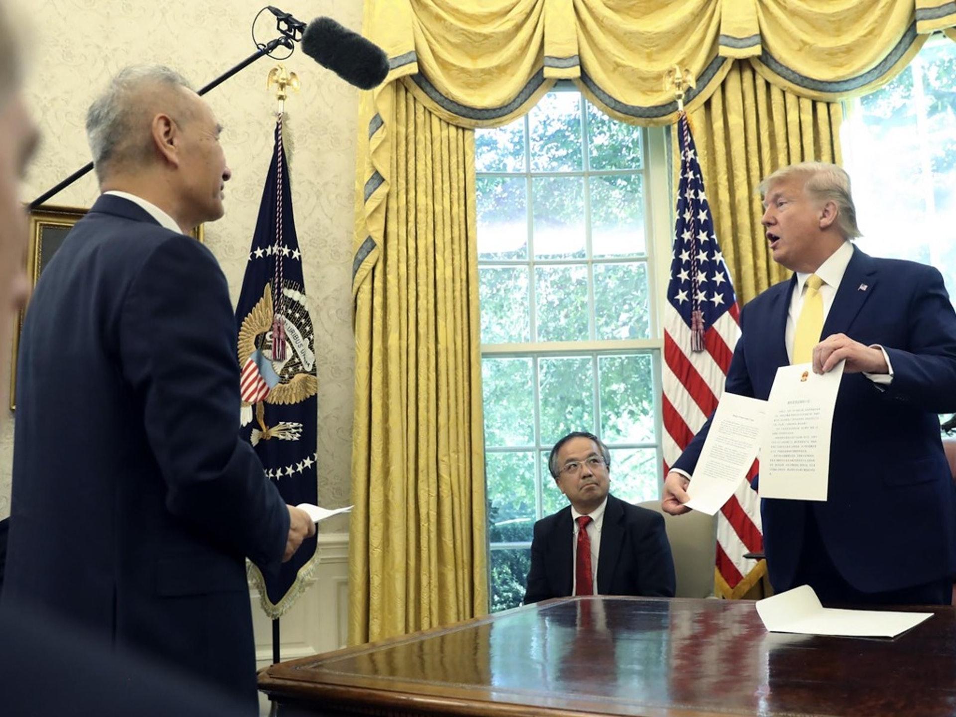 10月11日,特朗普(右)���中��副�理�ⅩQ�r,宣布美中�_成第一�A段�Q易�f�h。(AP)