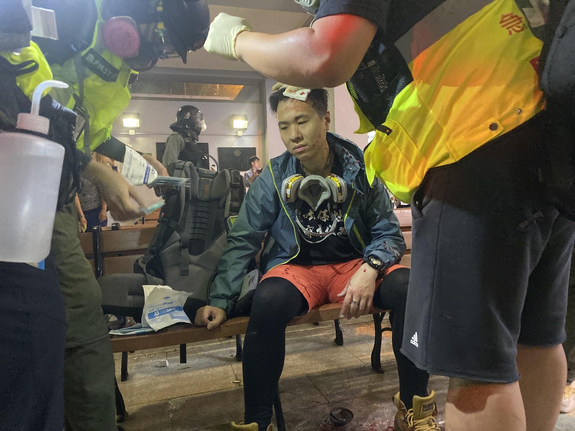 太子一名男社工于冲突其间被打破头,在场急救员为他救治。(陈浩然摄)