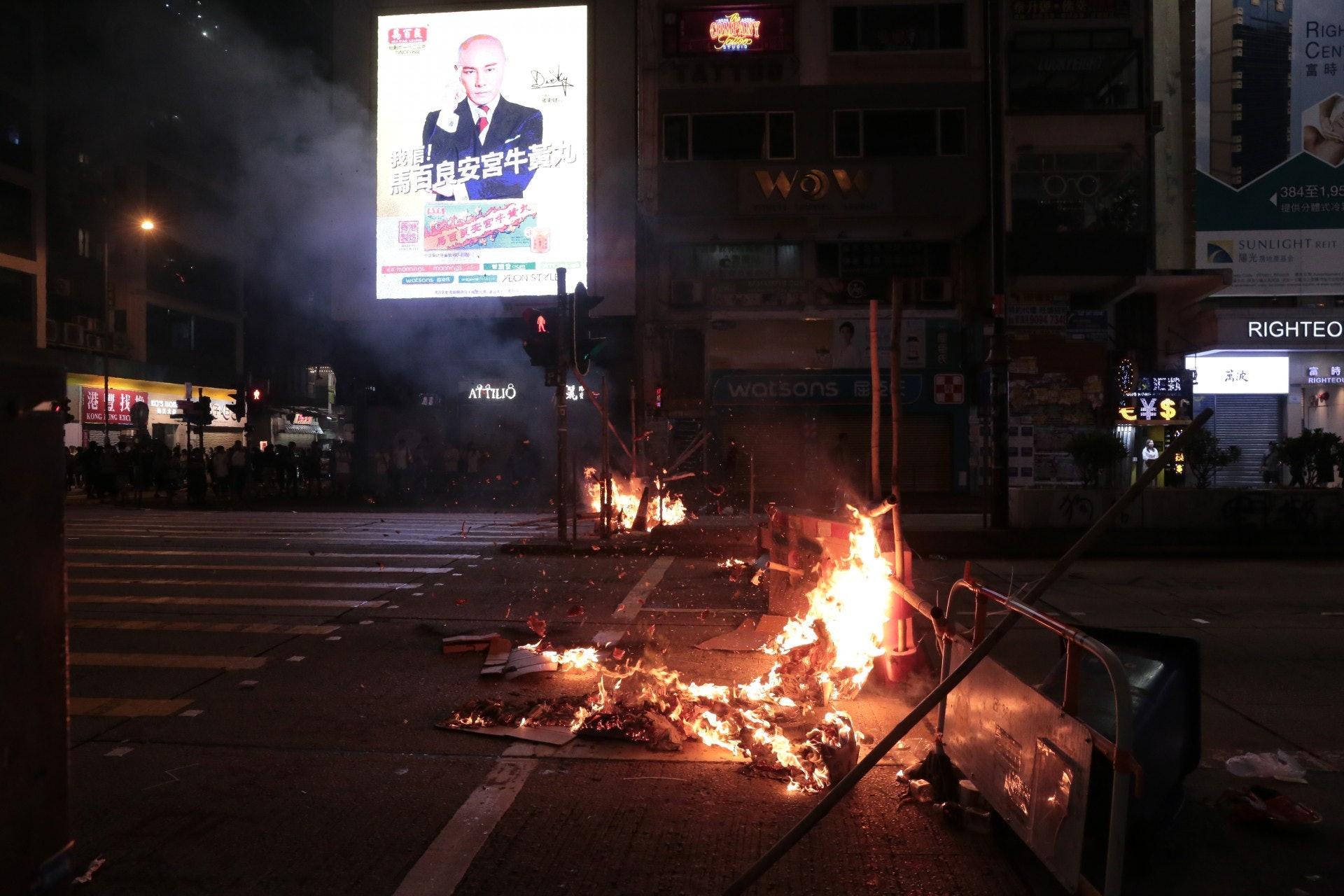 弥敦道有示威者烧路障。(余睿菁摄)