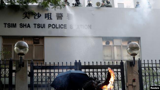 一名反送中抗议者向香港尖沙咀警察署投掷燃烧瓶。 (2019年10月20日)