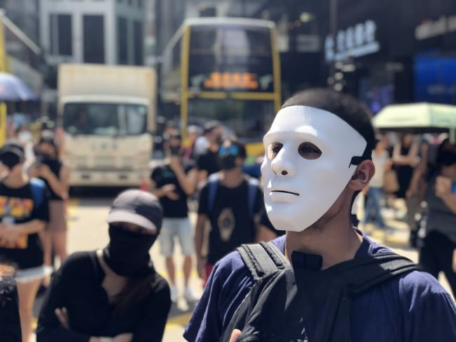 数以千计香港市民及抗争者10月4日中午在中环戴上面具及口罩快闪游行堵路,反对当局制定禁蒙面法。(摄影: 美国之音汤惠芸)