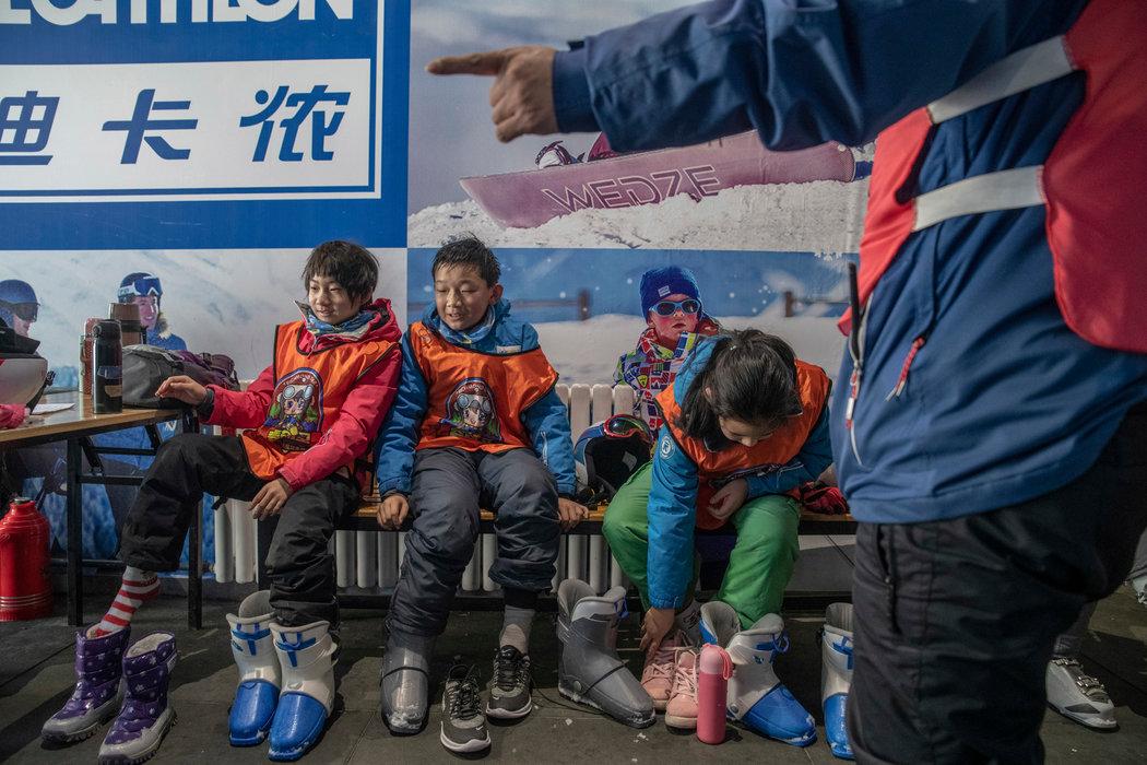 """孩子们在上完滑雪课后脱下装备,这是党的一项计划,旨在培养3亿""""冬季运动爱好者""""。"""