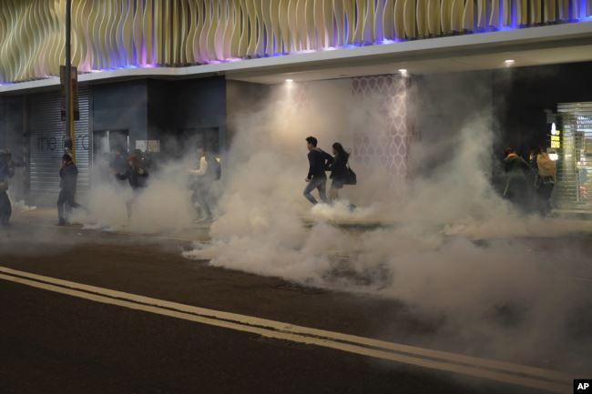 香港民众在圣诞平安夜逃避港警向示威者发射的催泪弹。(2019年12月24日)